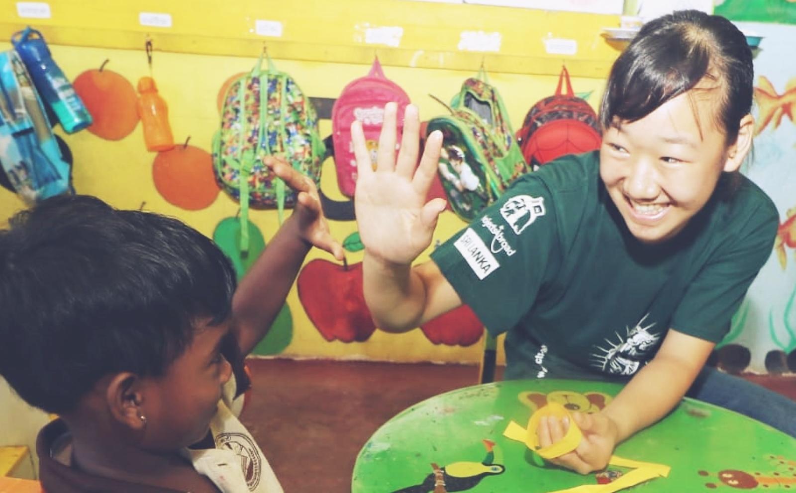 スリランカの幼稚園生とハイタッチをする高校生ボランティア澁川実結さん